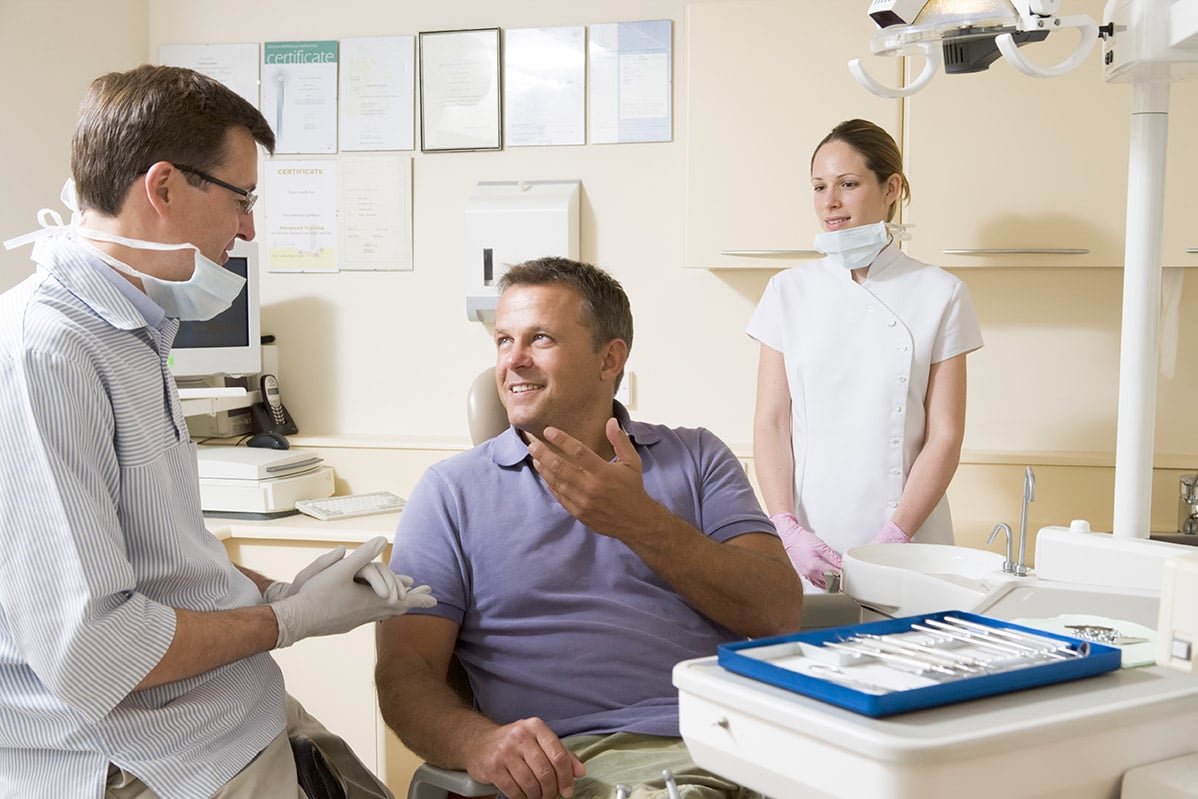 A dentist speaks with his patient about dental health habits.