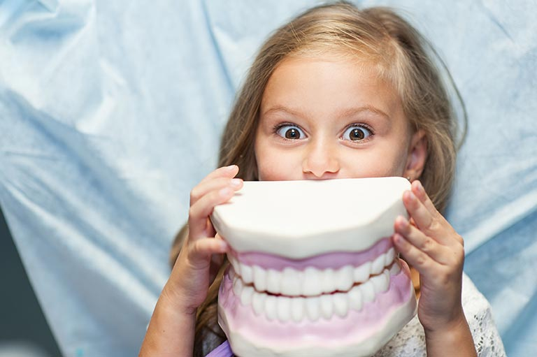 A little girl humorously holds up a massive set of dentures to her face.
