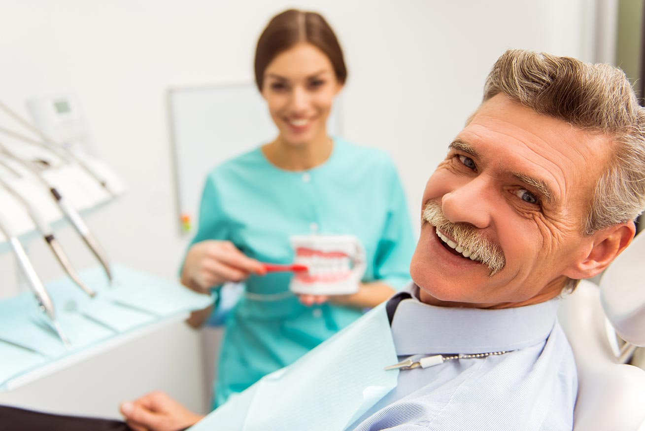 A dental patient with a mustache and white hair smiles for a photo while sitting in the patient's chair.