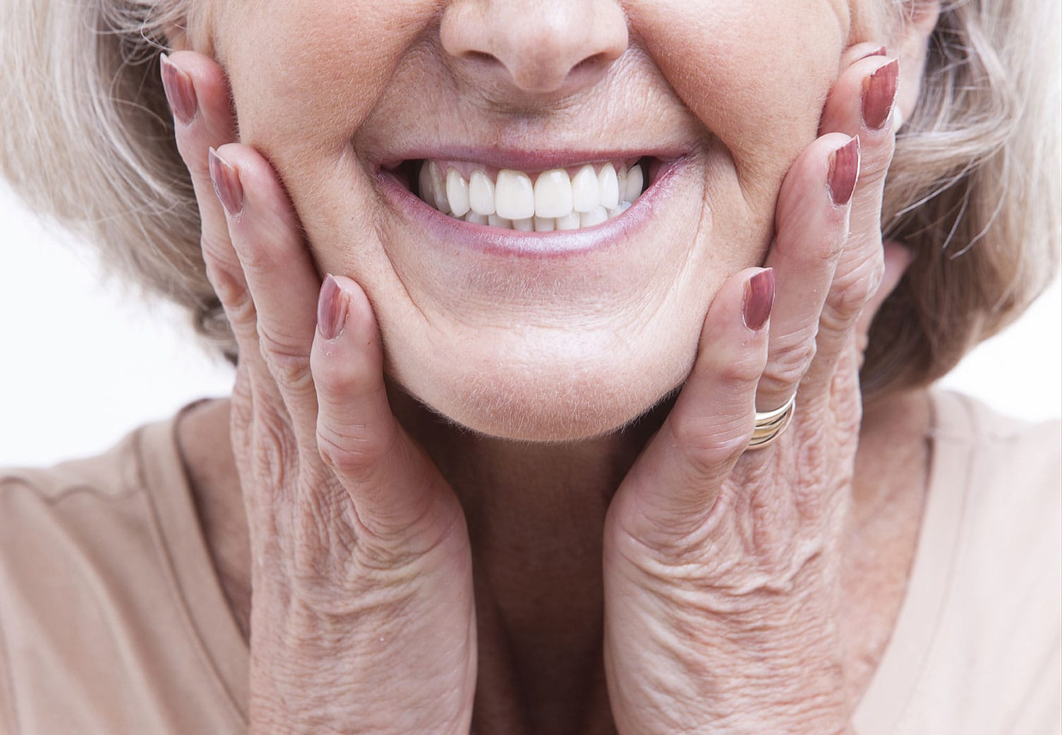 An older woman smiles, showing off her healthy and white teeth.