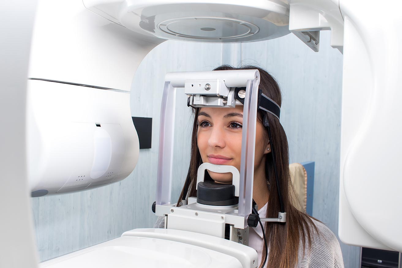 A dental patient gets her teeth imaged at the dentist office.