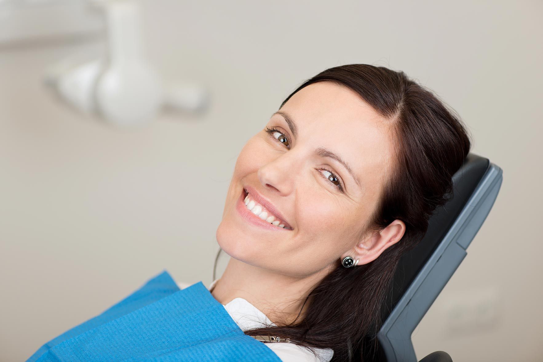 A woman sits in the dentist chair, comfortably awaiting care.