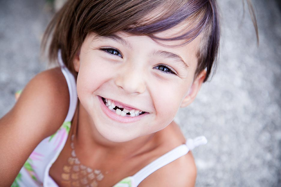 A young girl missing her baby teeth smiles widely.
