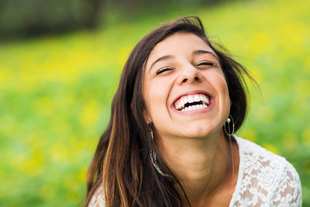 A young woman with white, healthy teeth sits outdoors on the grass and laughs happily.